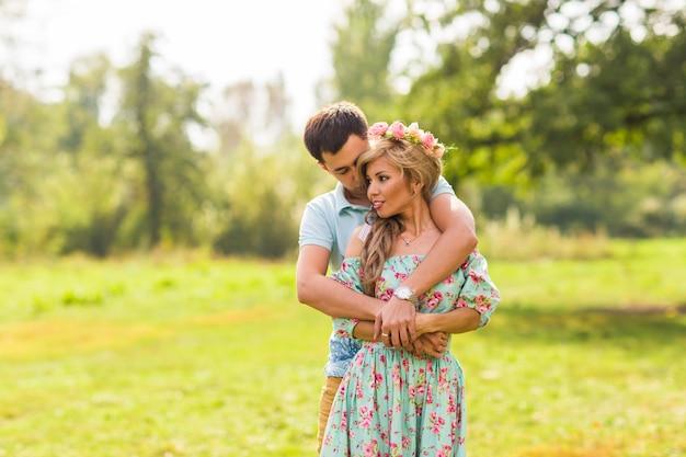 Coppia in amore bei giovani uomini che abbracciano in un parco estivo in una giornata di sole.