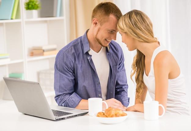 Coppia in amore facendo colazione insieme in cucina.