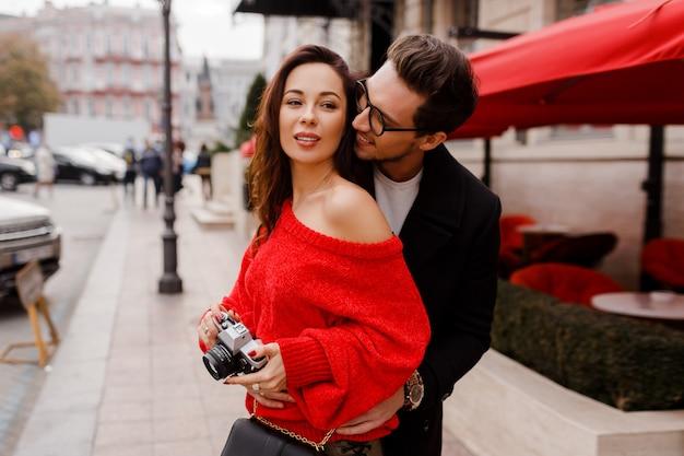 Coppia in amore imbarazzante e in posa per strada in vacanza. atmosfera romantica. bella donna castana tenendo la fotocamera a pellicola.