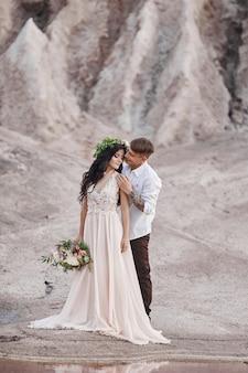 Coppia in amore in favolose montagne che abbracciano, paesaggio marziano. gli amanti camminano in montagna in estate, la ragazza in abito estivo lungo e leggero con un mazzo di fiori e una corona in testa