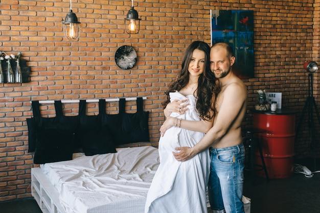 Coppia in amore incinta giacciono a letto coccole, in attesa di un bambino