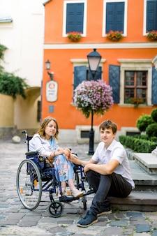 Coppia in amore nel centro storico. giovane ragazza con malattia su una sedia a rotelle e il suo uomo adorabile