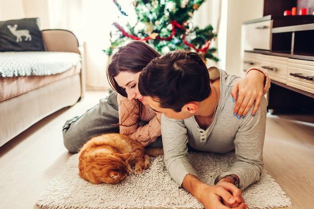 Coppia in amore sdraiato dall'albero di natale e giocando con il gatto a casa. uomo e donna rilassante