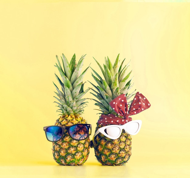 Coppia in amore shopping in un resort in vacanza. ananas con gli occhiali a forma di un ragazzo e una ragazza su uno sfondo chiaro