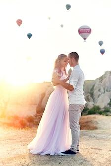 Coppia in amore si erge su sfondo di palloncini in cappadocia.