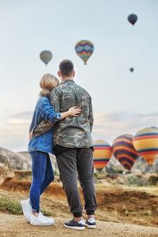Coppia in amore si erge sul paesaggio con palloncini