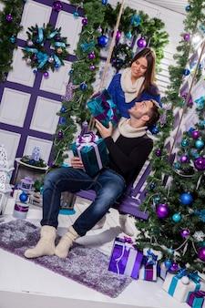 Coppia in amore su una terrazza si siede sull'altalena accanto a una decorazione natalizia