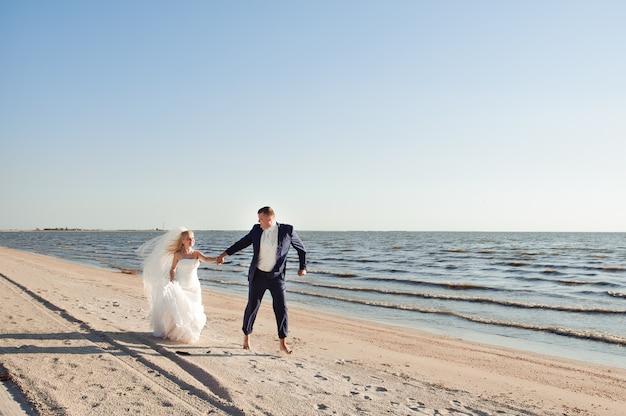 Coppia in amore sulla spiaggia il giorno delle nozze