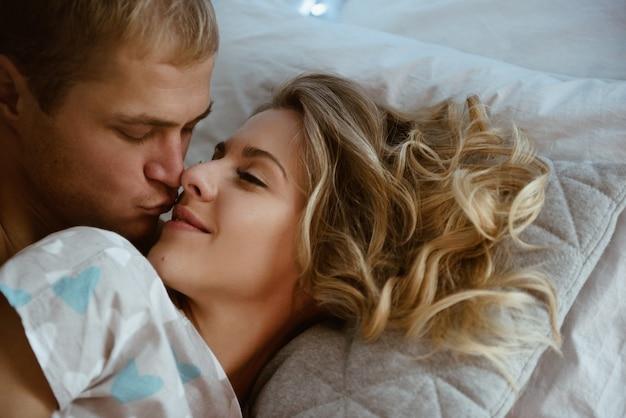 Coppia in camera da letto sul letto in camera da letto. una ragazza bionda in pigiama, un ragazzo con un torso nudo. periodo natalizio.