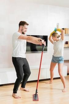 Coppia in casa ballando con accessori per la pulizia