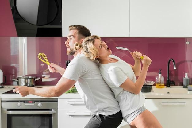Coppia in casa cantando in cucina seduti lateralmente