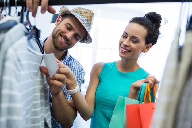 Coppia in cerca di cartellino del prezzo di vestiti