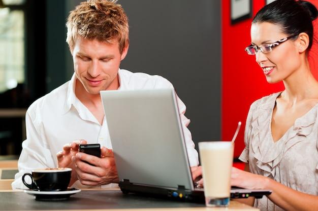Coppia in coffeeshop con laptop e cellulare