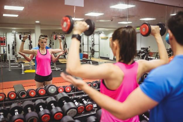 Coppia in forma lavorando in sala pesi