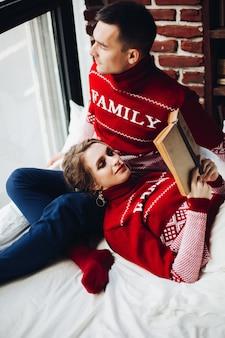 Coppia in maglioni rossi rilassanti, spendendo tomo insieme