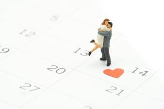 Coppia in miniatura 2 persone in piedi sul calendario. Il 14 ° giorno incontra il giorno di San Valentino