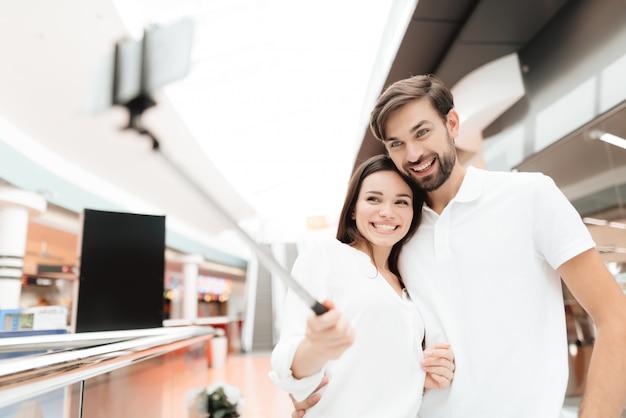 Coppia in negozio. la coppia sta prendendo selfie con selfie stick.
