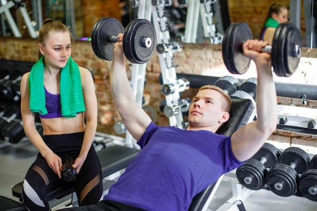 Coppia in palestra un personal trainer spiega a una giovane donna esercizi con un manubrio