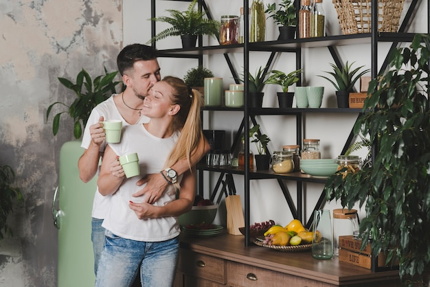 Coppia in piedi in cucina amarsi