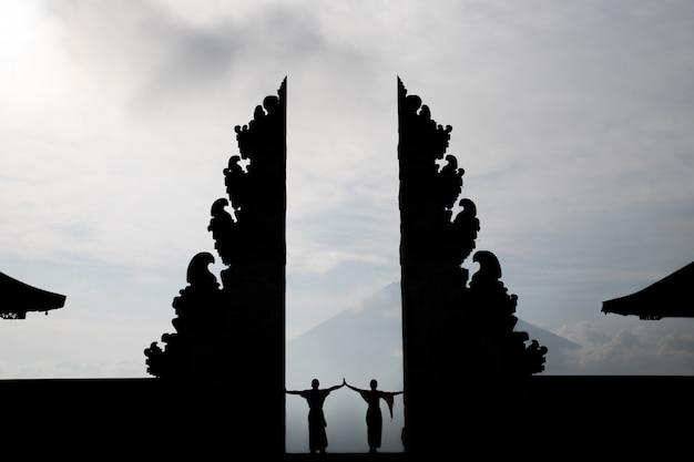 Coppia in piedi nelle porte del tempio di pura luhur lempuyang a bali