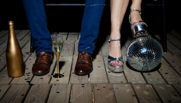 Coppia in piedi sul pavimento di legno con palla da discoteca e champagne