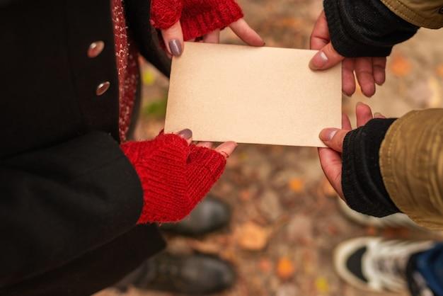 Coppia in possesso di un foglio di carta vintage vuoto nelle loro mani