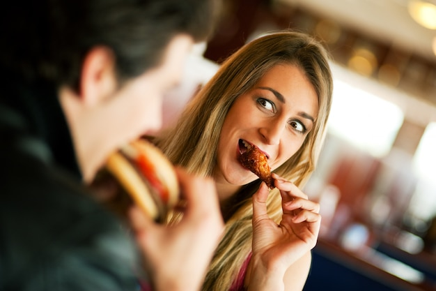 Coppia in ristorante a mangiare fast food