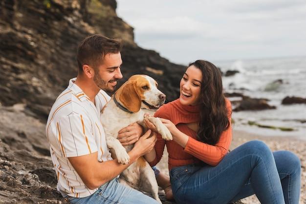 Coppia in riva al mare con cane