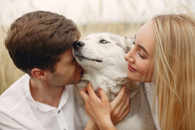 Coppia in un campo autunnale a giocare con un cane