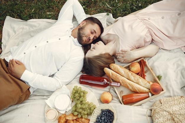 Coppia in un campo. bruna in un abito bianco. coppia seduta su un'erba.