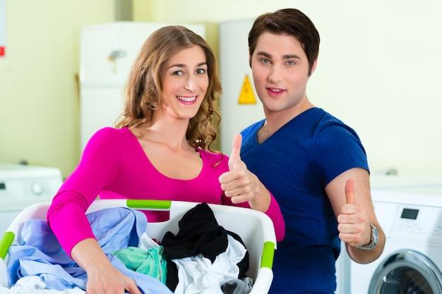 Coppia in un lavaggio biancheria lavanderia