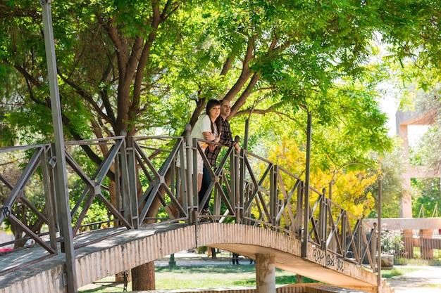 Coppia in un parco, sono in cima a un ponte