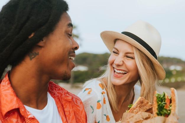 Coppia incontri e mangiare panini in un pic-nic sulla spiaggia