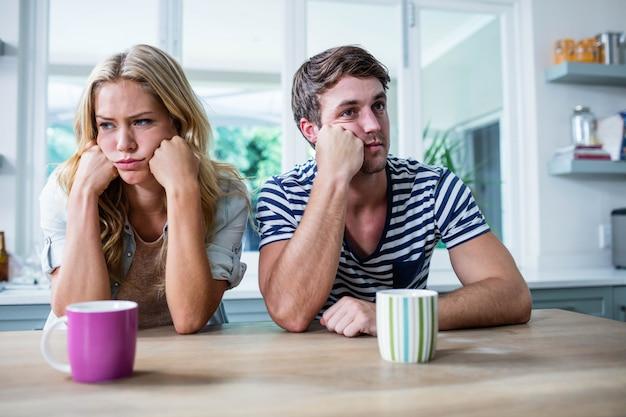 Coppia infastidita che si ignorano a vicenda in cucina
