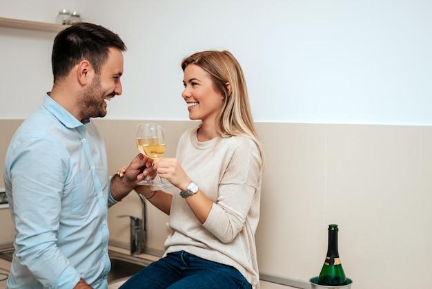 Coppia innamorata che beve vino nella loro cucina.