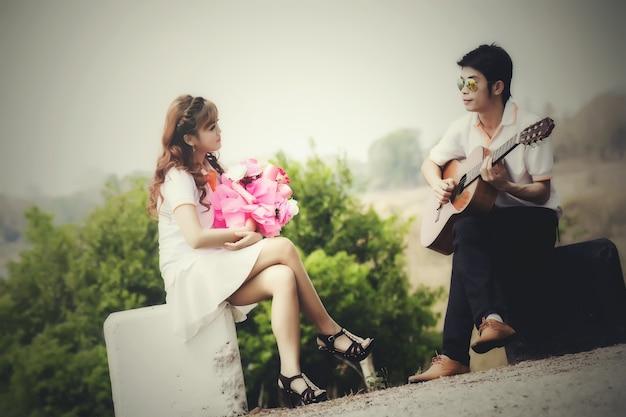 Coppia innamorata di suonare la chitarra in natura