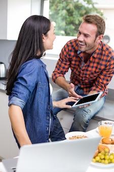 Coppia interagendo con laptop e tablet digitale