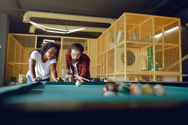 Coppia internazionale giocando a biliardo in un club