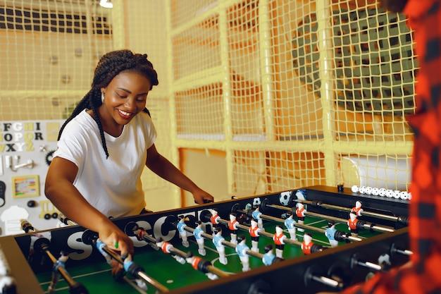 Coppia internazionale giocando a calcio balilla in un club