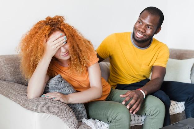 Coppia interrazziale parlando su un divano