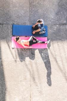 Coppia ispanica che si estende su stuoie di yoga