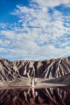Coppia l'amore in montagne favolose che abbracciano vicino al lago rosso