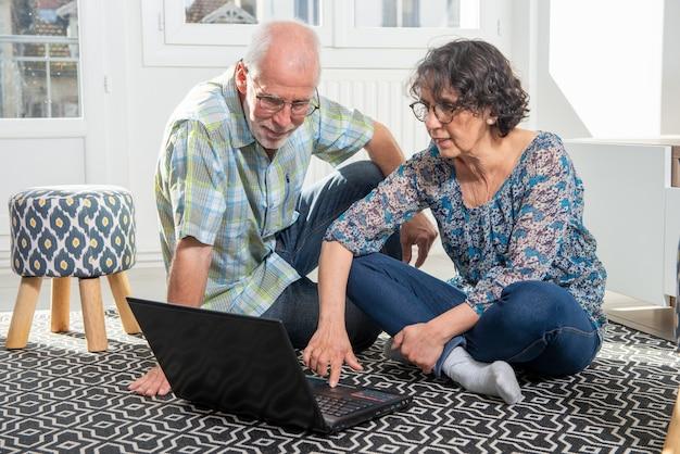 Coppia l'anziano facendo uso del computer portatile del computer a casa per l'acquisto online