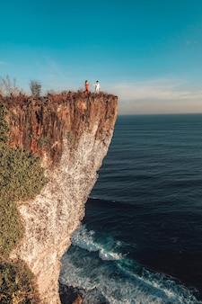 Coppia l'avventura e lo sguardo della vista sulla scogliera del boma del karang uluwatu bali in indonesia
