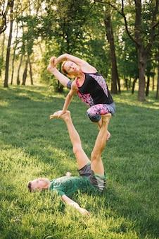 Coppia l'equilibratura e l'allungamento del muscolo mentre fa l'acro yoga
