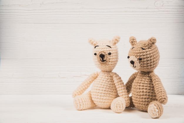 Coppia l'orsacchiotto all'uncinetto tricottare tricottato fatto a mano su legno bianco