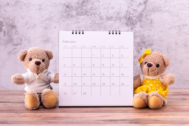 Coppia l'orsacchiotto con il calendario sulla tavola di legno
