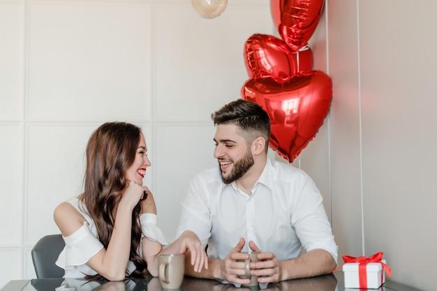 Coppia l'uomo e la donna che beve dalle tazze al mattino con il presente in confezione regalo e palloncini a forma di cuore a casa