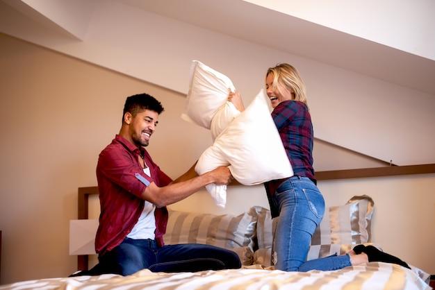 Coppia la battaglia del cuscino che si siede sul grande letto in camera da letto