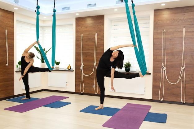 Coppia la donna che fa l'yoga della mosca che allunga gli esercizi in palestra